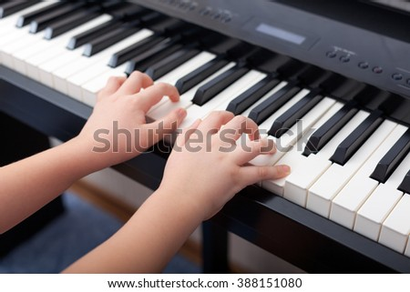 Child playing on a digital piano. - stock photo