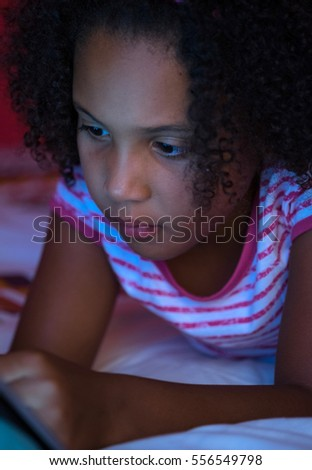 Child playing on her tablet while lying on her bed