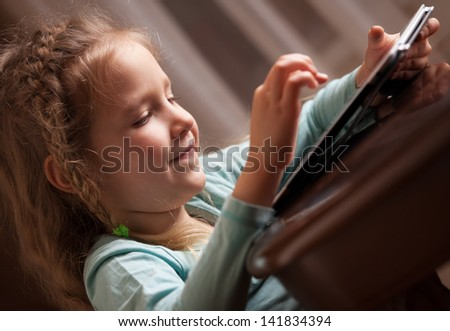 Child playing on tablet pc. Girl looking at computer - stock photo