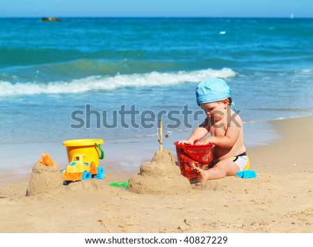 Child playing on the beach - stock photo