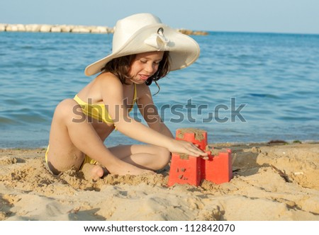 Child playing on the beach building a castle