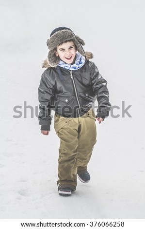 Child playing on the snow - stock photo