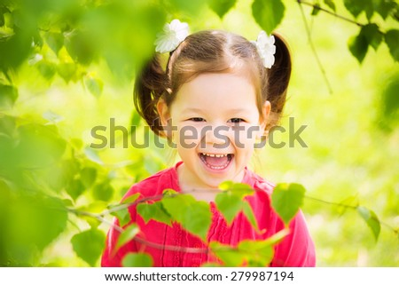 Child playing outside. closeup portrait of funny little kid. beautiful girls face happy laughing - stock photo