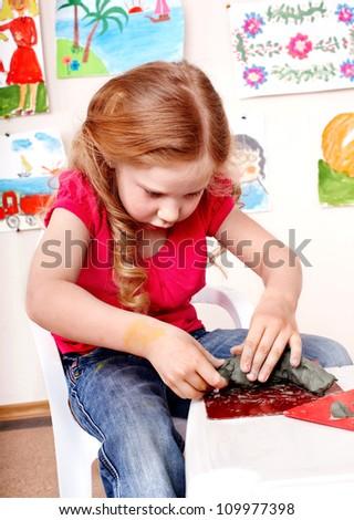 Child playing plasticine in kindergarten. Creativity development. - stock photo