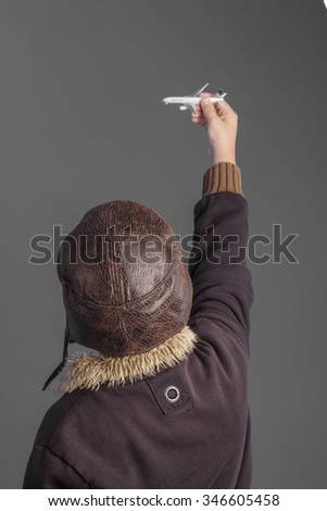 child playing the aircraft pilot with hat and retro bomber jacket - stock photo