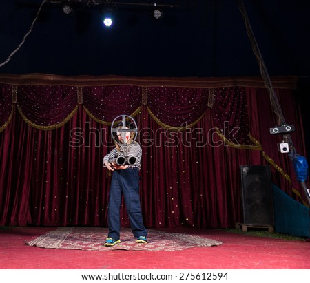 Child playing the role of a sniper with a huge and unusual weapon, in a conceptual theatrical representation - stock photo