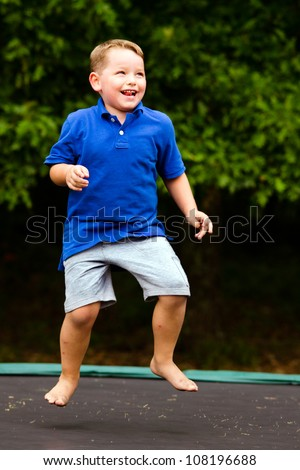 Child playing while jumping on trampoline - stock photo