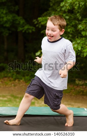 Child playing while jumping on trampoline outdoors on spring day - stock photo