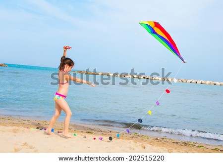 Child playing with a kite on the beach - stock photo