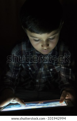 Child playing with a tablet pc and illuminated by its screen - stock photo