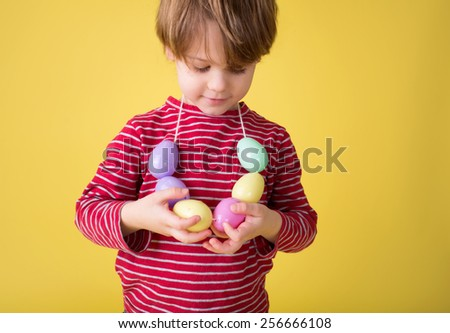 Child playing with an easter egg necklace, easter egg hunt concept. - stock photo