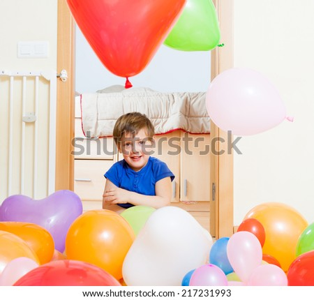 Child playing with colorful balloons at home