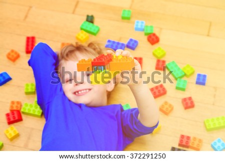 child playing with colorful plastic blocks