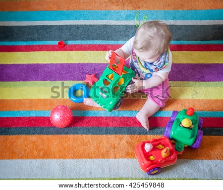 Child playing with educational toys. cute baby girl boy, playing with toy train, blocks, tracktor, building towers at home or day care. Educational child toys. preschool and - stock photo