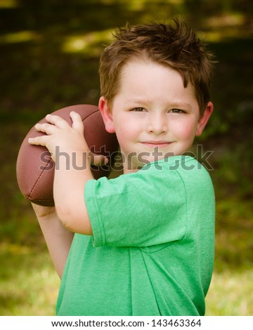 Child playing with football outdoors in yard - stock photo