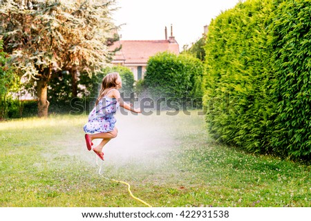 Child playing with garden sprinkler, jumping over - stock photo