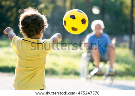 child playing with grandfather on wheelchair