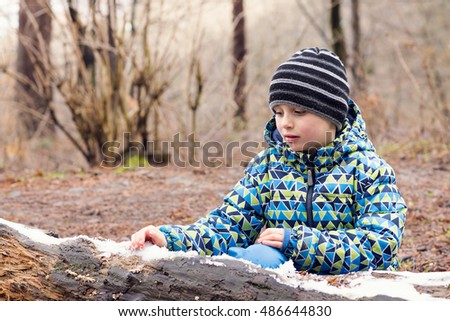 Child playing with melting snow in early spring forest