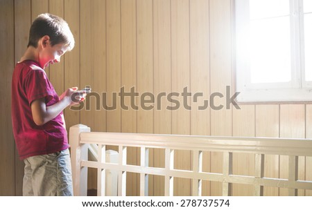 Child playing with mobile phone. Sunlight thru the window - stock photo