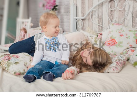 Child playing with mother in bed during the day. Family relaxing at home