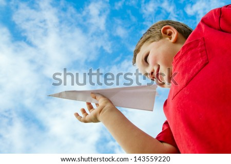 Child playing with paper airplane under cloudy blue sky - stock photo