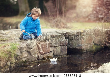 Child playing with paper boat and stick on bridge by water - stock photo