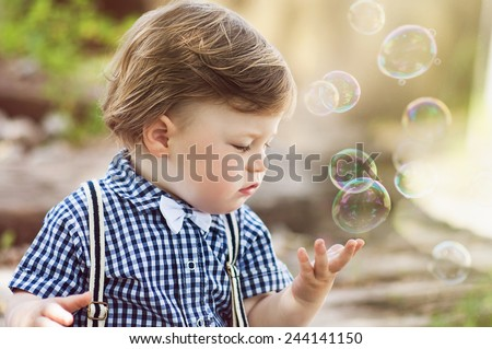 child playing with soap bubbles, close up - stock photo