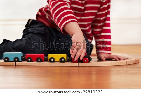 Child playing with toy wooden train - stock photo