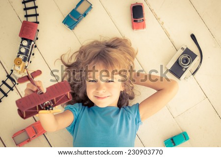 Child playing with vintage toys at home. Girl power and feminism concept - stock photo