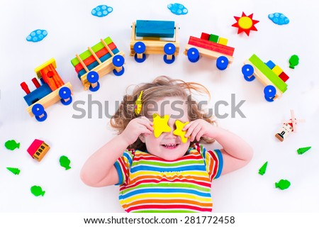 Child playing with wooden train. Toy railroad for kids. Toddler kid at day care. Educational toys for preschool and kindergarten child. Little girl at daycare. - stock photo