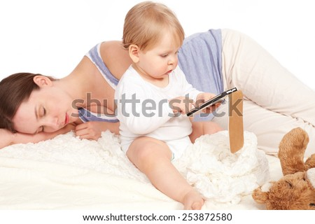 Child playing with your smartphone while mother is sleeping - stock photo
