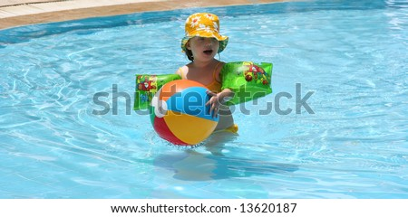 Child plays in a water pool - stock photo