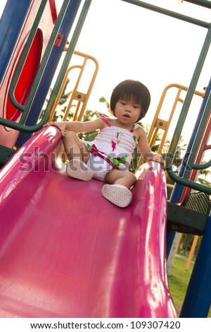 Child plays on slide in an outdoor playground