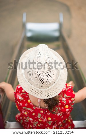 Child plays on slide in an outdoor playground - stock photo