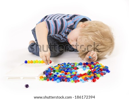 Child plays with a mosaic - stock photo