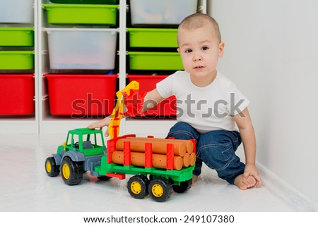 child plays with a timber truck - stock photo