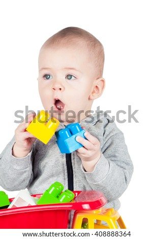 child plays with plastic constructor on white background - stock photo