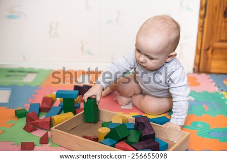 child plays with toy blocks in the nursery - stock photo