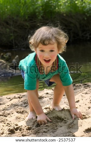 Child plays with water in small river at hot summer day