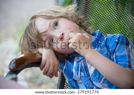 Child portrait. Closeup of an adorable little boy in a blue shirt relaxing in an old armchair outside in summer