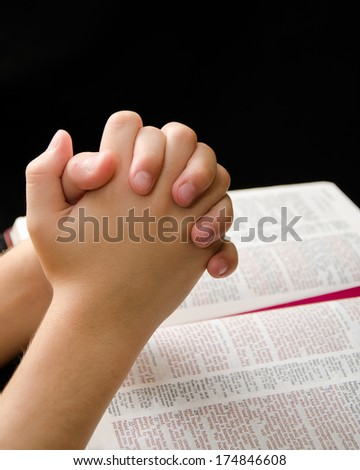 Child praying with devotion over an open Bible - stock photo