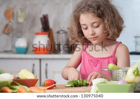 child  preparing healthy food vegetable salad - stock photo