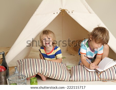 Child, preschooler kids, playing at home indoors with a teepee tent