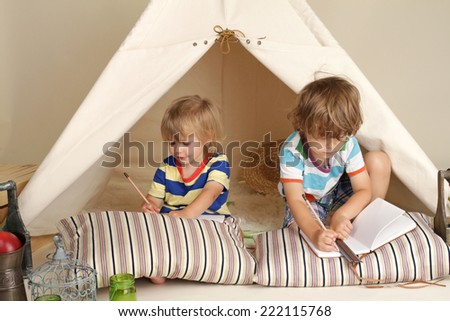 Child, preschooler kids, playing at home indoors with a teepee tent - stock photo