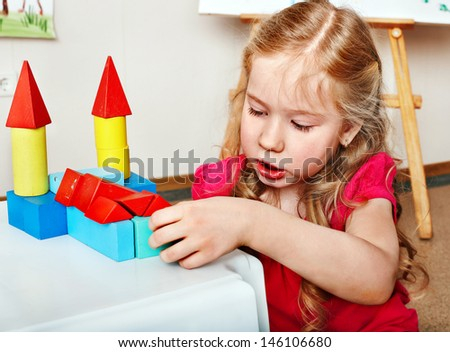 Child preschooler play wood block in play room. Child care. - stock photo