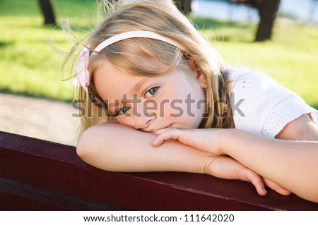 child problem. sad little girl 6 years old sitting at the park - stock photo