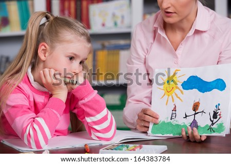 Child psychologist with a sad little girl, the doctor looks at the child's picture - stock photo