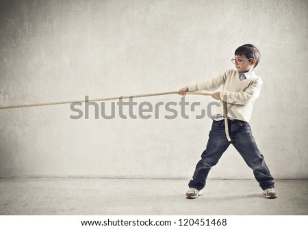 Child pulling a rope - stock photo