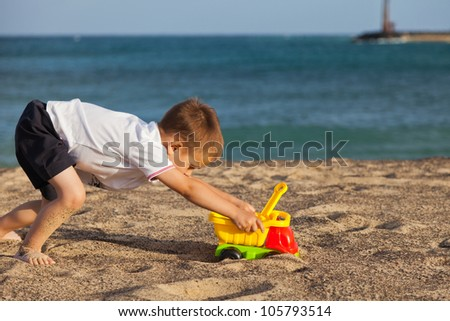 Child pushing his car toy on a beach - stock photo