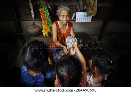 Child put water in the small bowl and then pour them into grandma's hand. - stock photo